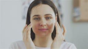 妇女离开从她的面孔的化妆面具和看照相机 股票录像