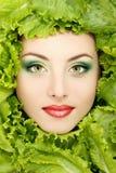 妇女秀丽表面用绿色新鲜的莴苣离开 库存照片