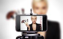 妇女秀丽Vlogger 由分享在社会媒介的智能手机的录象剪辑 时尚博客作者生活化妆构成讲解 图库摄影
