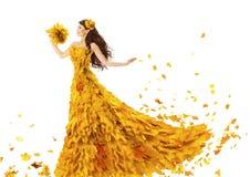 妇女秋天秋天叶子时尚礼服,式样女孩以黄色 免版税库存图片