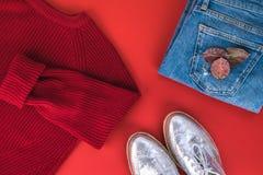 妇女秋天/冬天给放置在红色背景穿衣 牛仔裤,染黄被编织的套头衫,银色平的鞋子 免版税库存图片