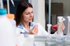 妇女科学家执行的实验在研究实验室 免版税库存照片