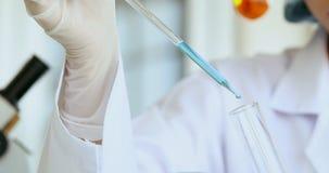 妇女科学家落下的液体到试管里 影视素材
