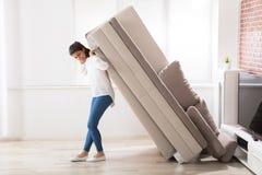 妇女移动的沙发在家 免版税库存照片