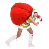 妇女穿戴了象与礼物的一个滑稽的地精拉扯红色袋子,隔绝在白色 库存图片