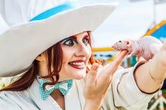妇女穿戴了象疯狂的白帽商与咩咩叫鼠 库存照片