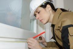 妇女窗口安装员标号测量 免版税库存照片