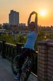 妇女立场和休息,在自行车乘驾,举行她的手behi后 库存图片