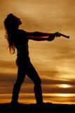 妇女立场边点的剪影开枪  免版税库存图片