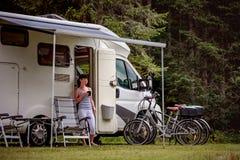 妇女站立与一个杯子咖啡在露营车RV附近 图库摄影