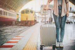 妇女站立与行李的旅客游人在火车站 免版税库存图片
