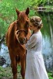 妇女站立与马的在湖附近和与她的前额的感人的马面孔 库存图片