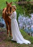 妇女站立与马的在湖附近和与她的前额的感人的马面孔 免版税库存图片