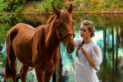 妇女站立与马的在湖附近和与她的前额的感人的马面孔 免版税库存照片