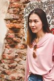 妇女站立在一个老砖墙 库存图片
