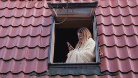 妇女站立在房子的屋顶窗口并且使用电话 股票视频