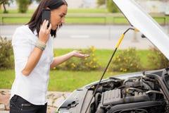 妇女站立在残破的汽车旁边和谈话在电话 免版税库存图片