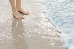 妇女站立在海浪的` s脚在海滩 免版税库存照片