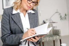 妇女站立在笔记本的偶然家庭办公室文字的心理学家画象 库存照片