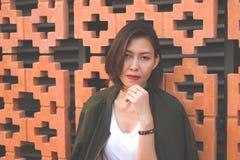 妇女站立对砖墙 免版税库存图片