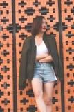 妇女站立对砖墙 库存图片