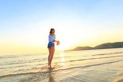 妇女站立并且拿着在海滩的帽子在日落之间 免版税库存照片