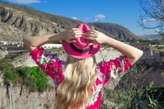 妇女站立用在一个桃红色帽子扣紧的她的手 他看山和山沟 免版税图库摄影