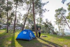 妇女站立的下个蓝色帐篷 免版税库存照片