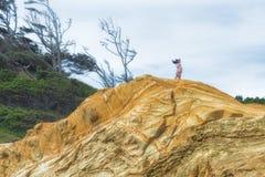 妇女站立高在砂岩虚张声势在海角Kiwanda 免版税图库摄影