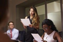 妇女站立读书文件在晚上业务会议上 库存照片