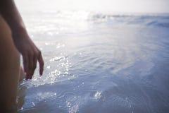 妇女站立` s的腿和的手看海洋 免版税图库摄影