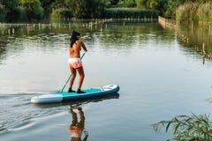妇女站立paddleboarding 免版税图库摄影