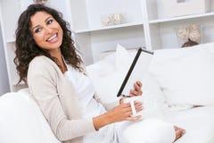 妇女笑的饮用的茶或咖啡使用片剂计算机 免版税库存图片