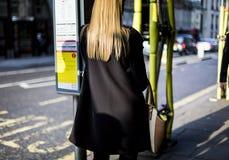 妇女等待在一条晴朗的伦敦街道上的一辆公共汽车 库存图片