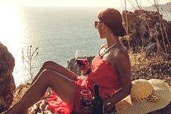 妇女等待她的一顿浪漫野餐的人有海边和山景 图库摄影