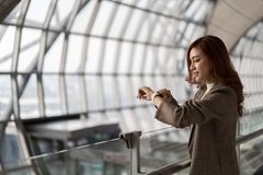 妇女等待的飞行和看起来巧妙的手表在机场 免版税图库摄影