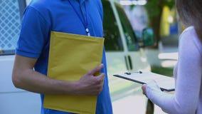 妇女签署的证明送到单和接受黄色包裹从传讯者 股票视频