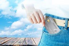 妇女精选现实信用或转账卡与老木桌在云彩天空背景 免版税库存照片
