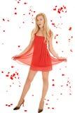 妇女红色礼服举行裙子玫瑰花瓣。 免版税库存照片