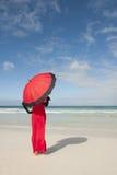 妇女红色礼服伞海滩 库存图片