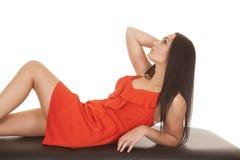 妇女红色礼服向后倾斜仔细的审视  图库摄影