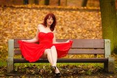 妇女红色礼服坐长凳在秋天公园 免版税图库摄影