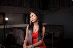 妇女红色礼服的和有摆在为照相机的长的头发的在酒吧或餐馆 免版税库存照片