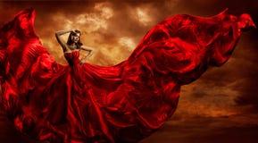 妇女红色礼服飞行的丝织物,时装模特儿舞蹈风暴 免版税库存图片