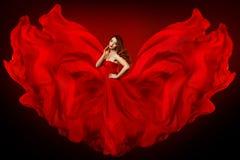 妇女红色礼服,在长的丝绸褂子挥动的布料作为翼,飞行的振翼的织品的女孩的时装模特儿 免版税库存照片