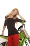 妇女红色裤子绿色摩托车关闭倾斜手肘 库存照片
