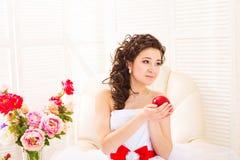 妇女纯净概念 拿着红色苹果-爱的标志的新娘的手 库存图片