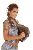 妇女纹身花刺女牛仔边举行帽子微笑 免版税库存照片