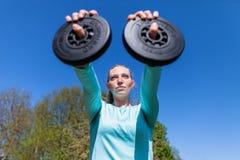 妇女练习在体育礼服的举重 图库摄影