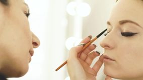 妇女组成使用化妆用品刷子的艺术家为构成眼睛和眼眉秀丽模型的 关闭做构成的visagist 股票视频